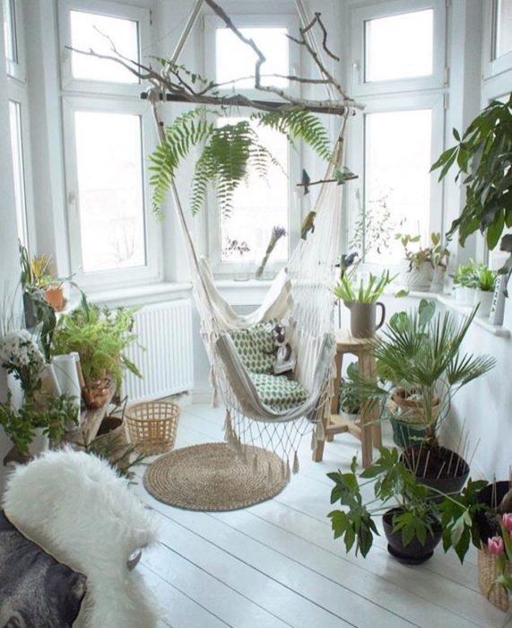 Sala de descanso con una hamaca en el centro, un tapete, cojines y plantas alrededor de diferentes tipos