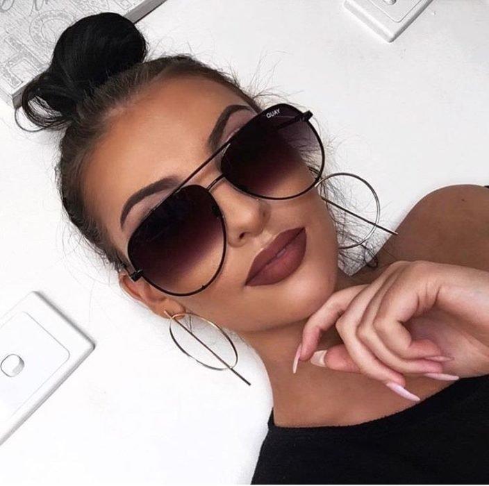 Chica recargada en su propia mano usando lentes con degradado