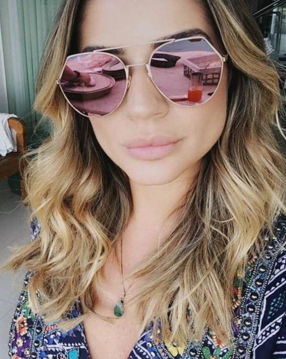 Chica tomándose una selfie con sus gafas grandes de color rosa en efecto espejo