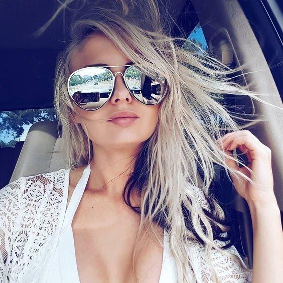 Chica dentro de un auto usando gafas grises con efecto espejo
