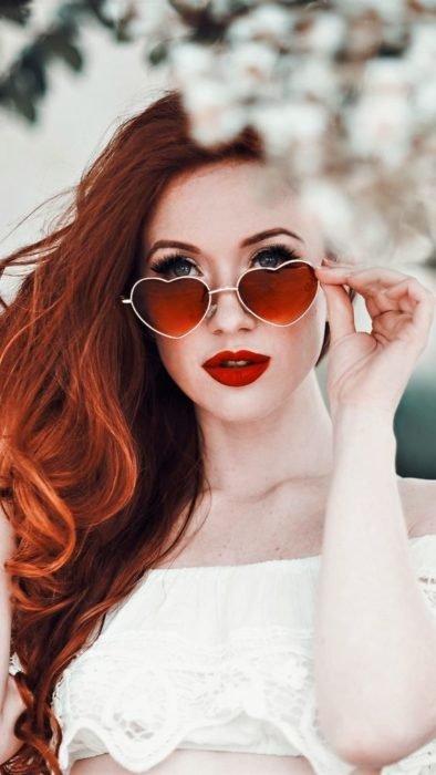 Chica modelando un par de gafas rojas con armazón en forma de corazón