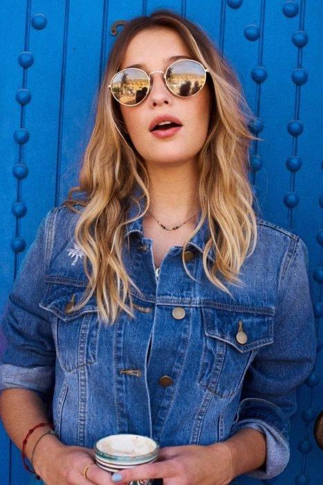 Chica recargada en un apared azul modelando su outfit y lentes redondos