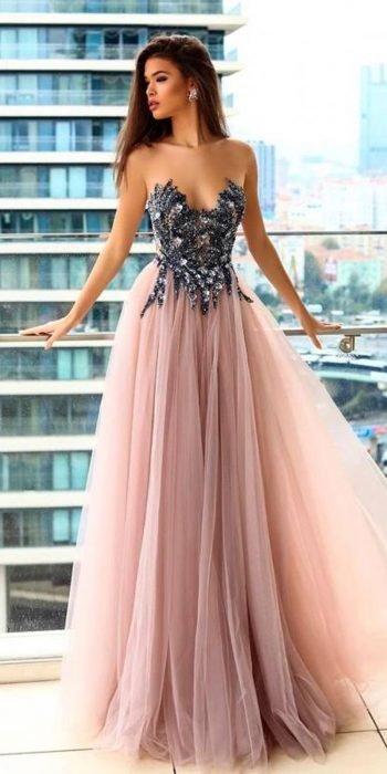 Chica en una terraza modelando un vestido con con detalles brillantes en el busto y falda de tul rosa
