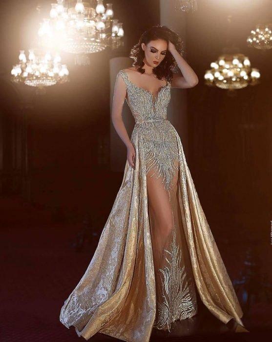 Chica modelando vestido en colores grises y dorados transparente