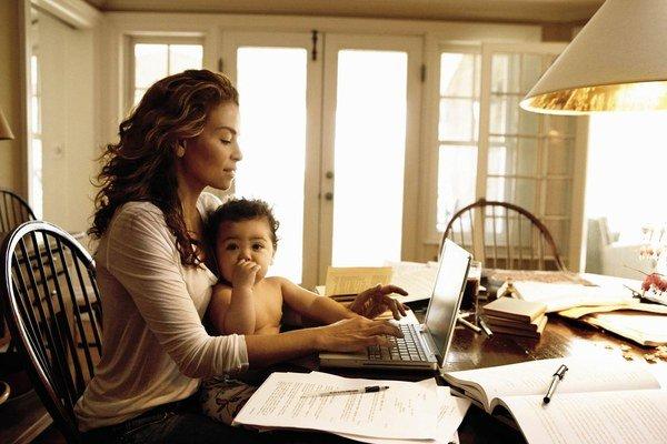Mamá joven cargando a su bebé mientras trabaja en laptop