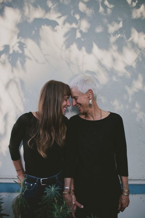 Madre de cabello blanco y corto e hija de cabello castaño con flequillo tomadas de la mano y sonriendo con los ojos cerrados