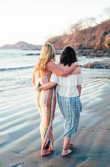 Madre de cabello castaño e hija rubia caminando descalzas en la arena en la playa mientras se abrazan