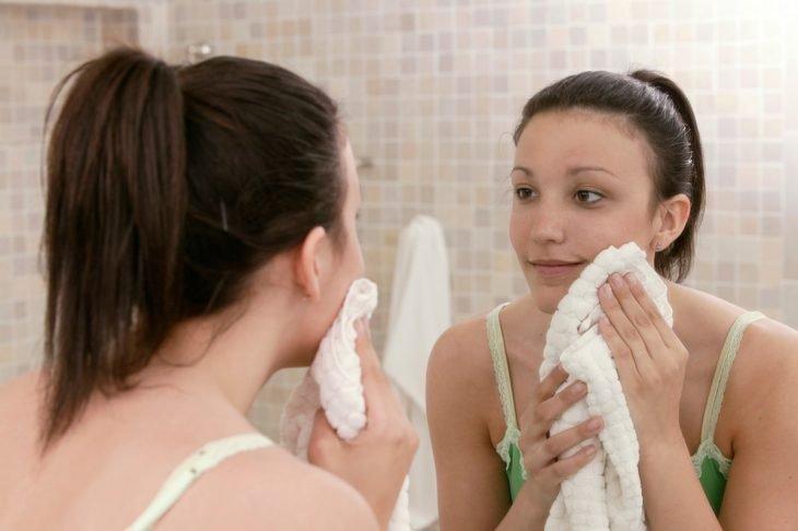 Chica frente al espejo, usando una toalla blanca para secar su rostro después de haberlo lavado