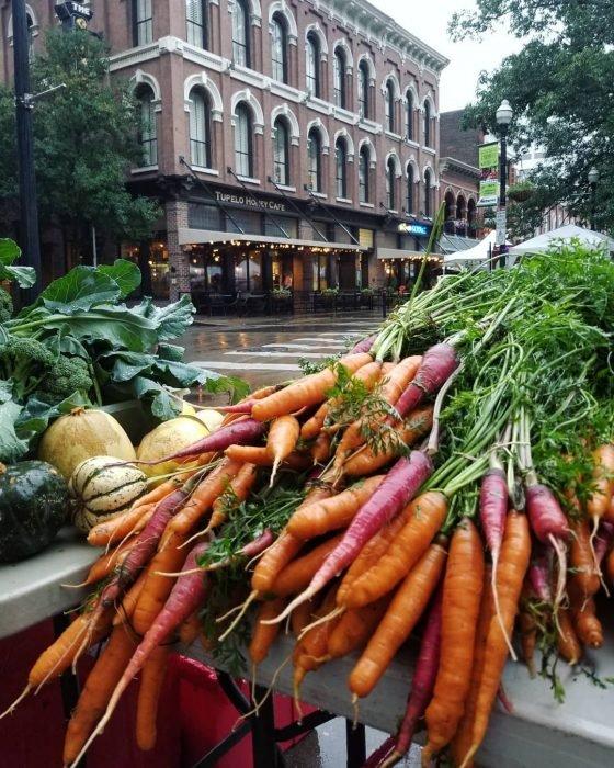 Zanahorias anaranjadas y moradas junto a calabazas en la calle, verduras