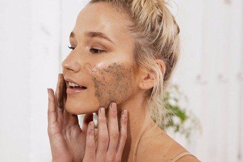 Chica dentro de un baño, mirándose frente al espejo para limpiar su cara
