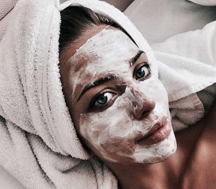 Chica usando mascarilla espumosa en color negro sobre su rostro y una toalla enredada sobre su cabeza
