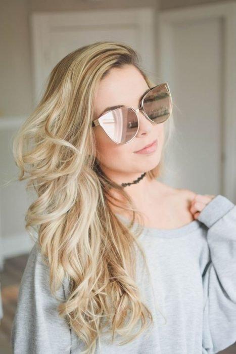 Chica modelando sus gafas claras con efecto de ojos de gato
