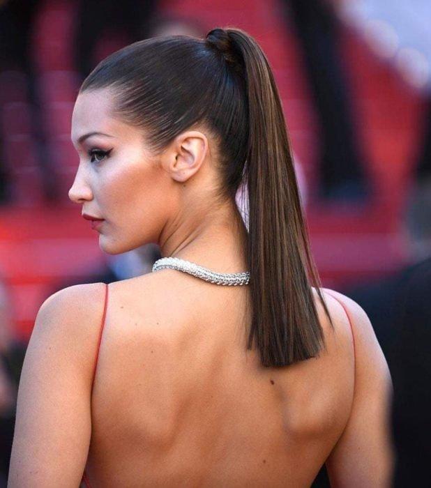 Ideas de peinados para el calor; modelo Bella Hadid con cabello castaño agarrado en una cola de caballo lacia