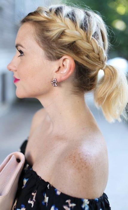 Ideas de peinados para el calor; mujer de cabello corto y rubio peinada con una trenza de lado y una cola de caballo