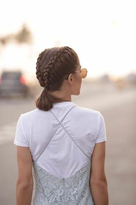 Ideas de peinados para el calor; chica de espaldas con el cabello castaño corto peinada con dos trenzas y una cola de caballo