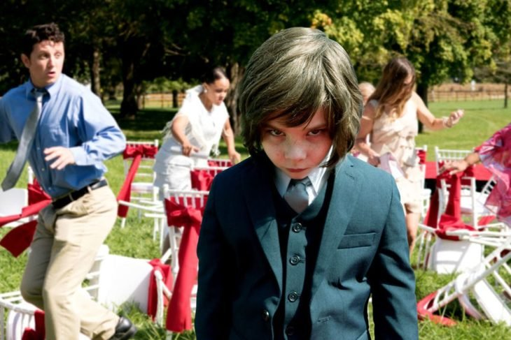 Película Pequeño demonio; niño con traje y mirada enojada, en una fiesta