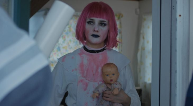 Película Little sister; chica con estilo gótico, cabello de honguito, con fleco, color rosa, usando maquillaje blanco y labial negro, sostiene en sus manos un muñeco