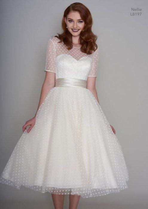 mujer pelirroja con vestido blanco de los años 50