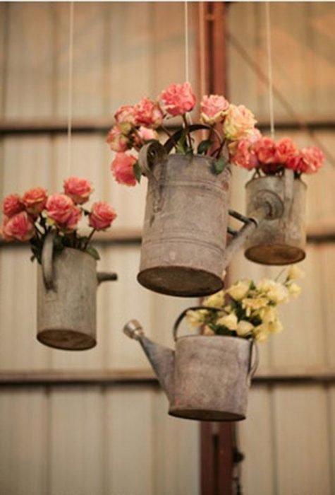 Regaderas de agua con flores dentro colgadas