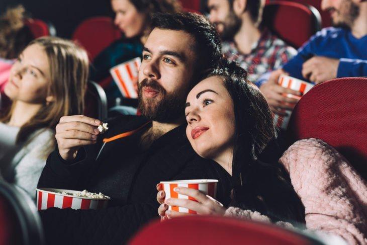 Chica recargada sobre el hombro de un chico, dentro de un cine comiendo palomitas