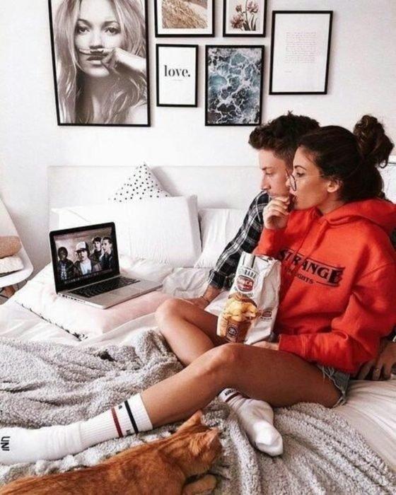 Pareja de novios abrazados, comiendo papas fritas y viendo una película sobre la cama