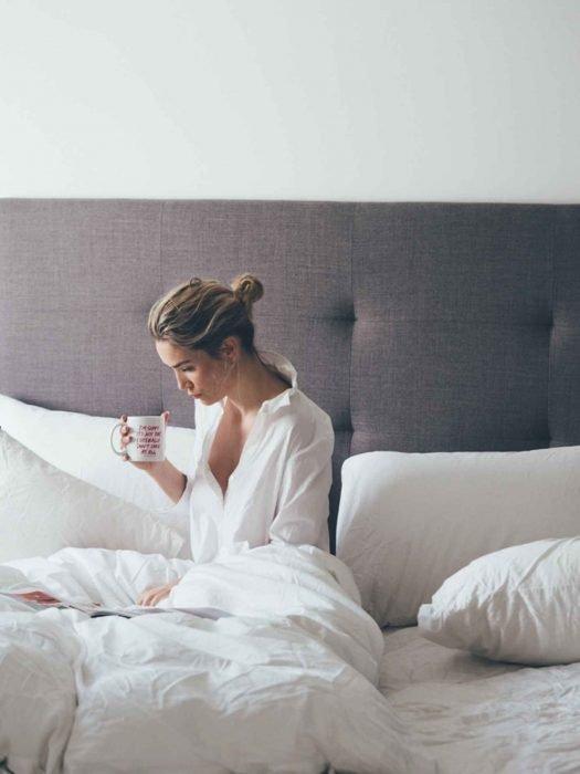 Mujer rubia sentada bebiendo una taza de café