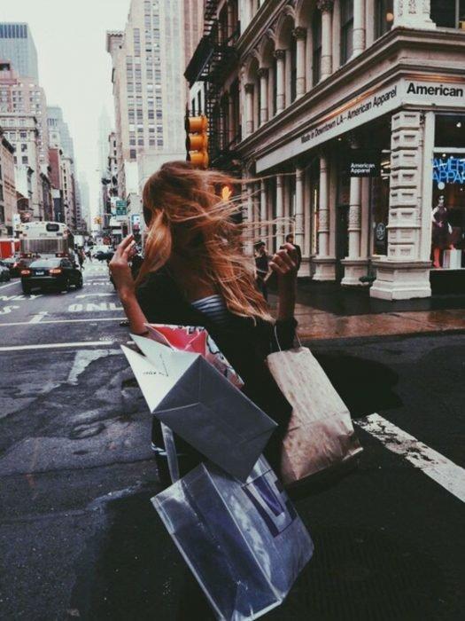 Mujer en la calle con bolsas de shopping