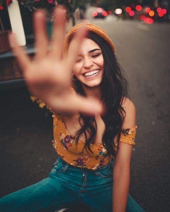 Chica con gorra anaranjada sentada en la calle sonriendo