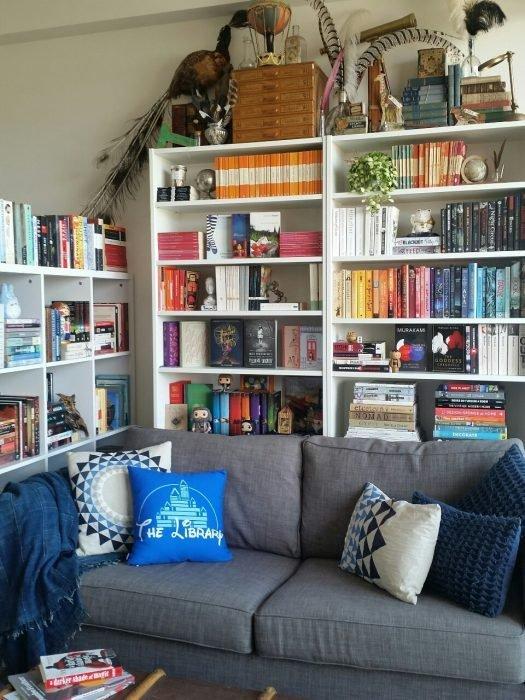 estanterías de libros detrás de un sillón gris