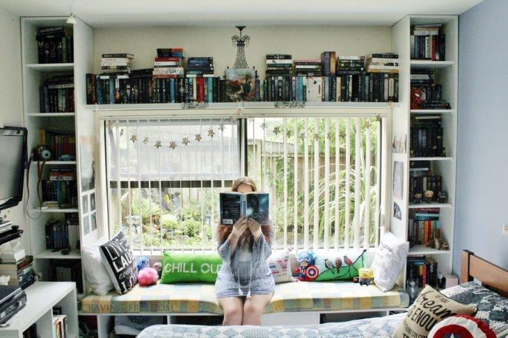 estanterías enmarcando una ventana y chica sosteniendo un libro