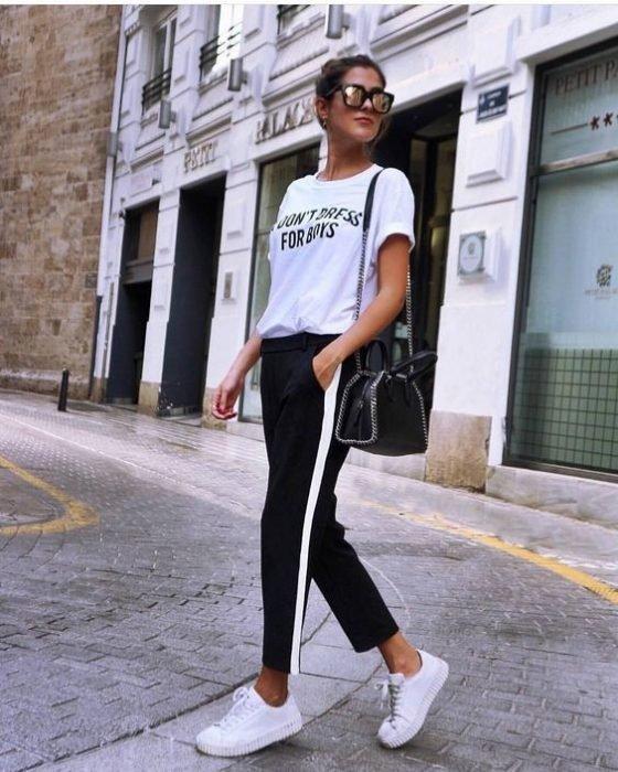 Chica usando unos tenis con pantalón negro y línea blanca y blusa de color blanco