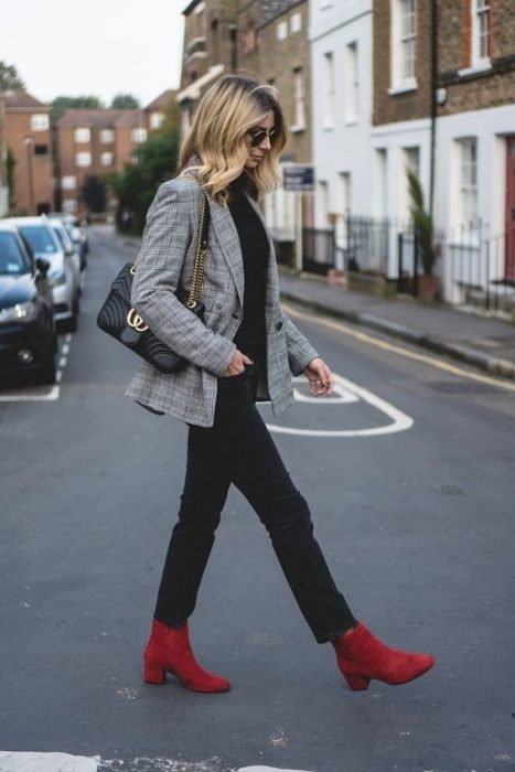 Chica caminando por la calle mientras usa unas botas de tacón cuadrado