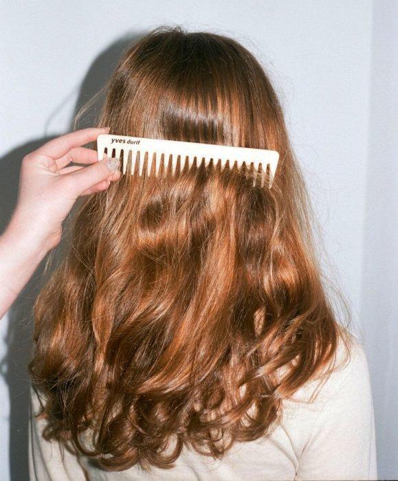 Mano peinando el cabello ondulado de chica pelirroja