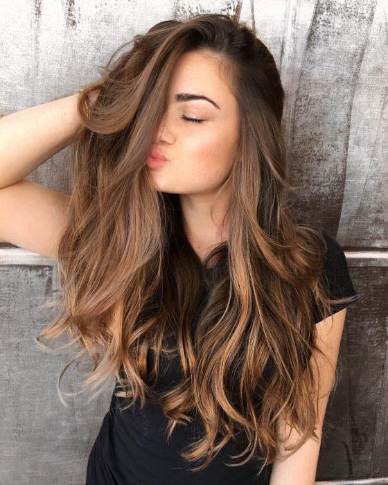 Chica con cabello largo y ondulado haciendo duckface