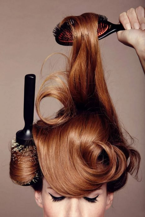 Mujer pelirroja peinándose el cabello con dos cepillos