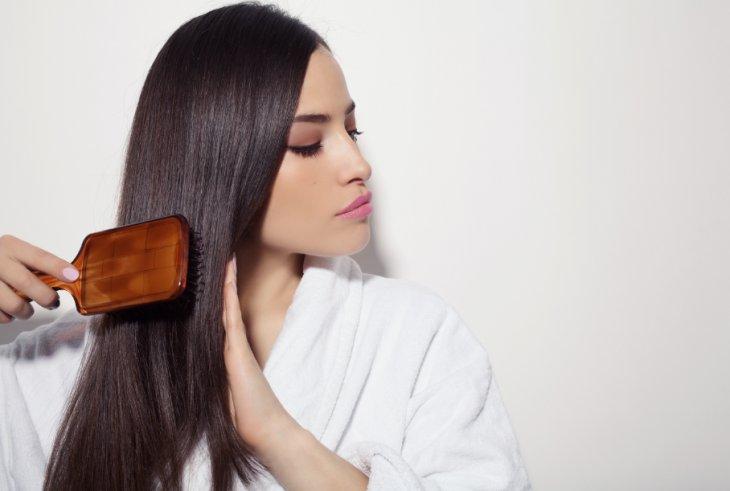 Chica cepillándose el cabello lacio y largo