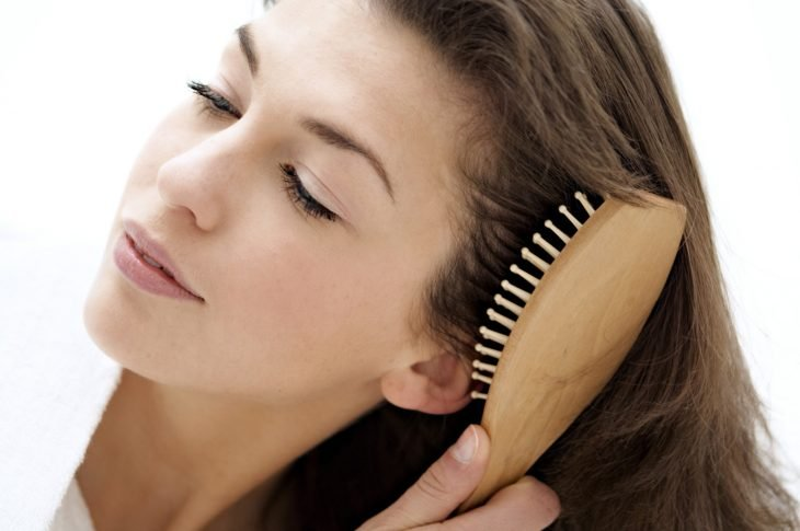 Mujer cepillándose el cabello con cepillo de madera