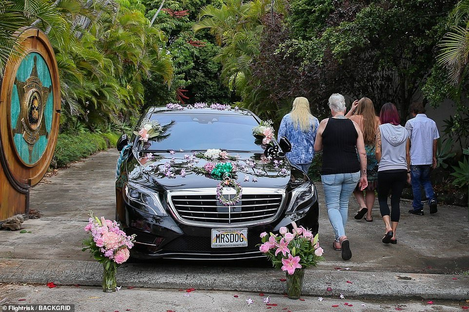 The family return to their home in Honolulu as they leave a car adorned with flowers at the front gate