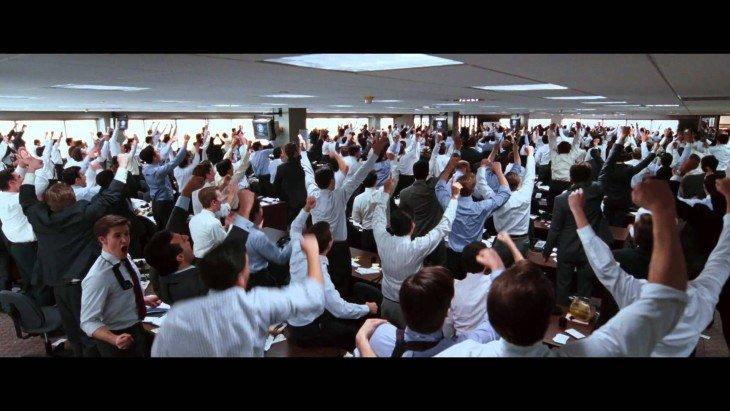 Escena del lobo de wall street donde los empleados están motivados levantando su mano