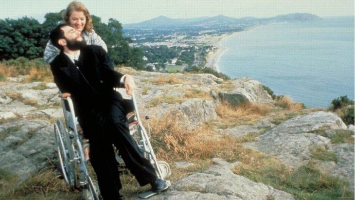 mujer y hombre en una silla de ruedas junto a un acantilado