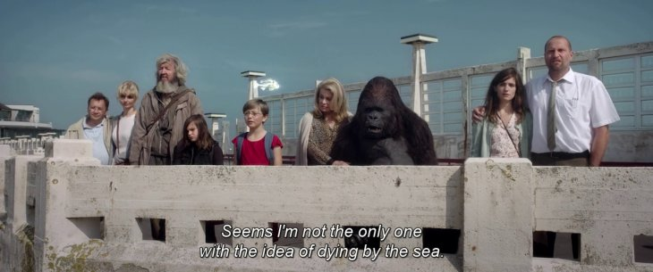 7 personas curiosas en una azotea con un gorila