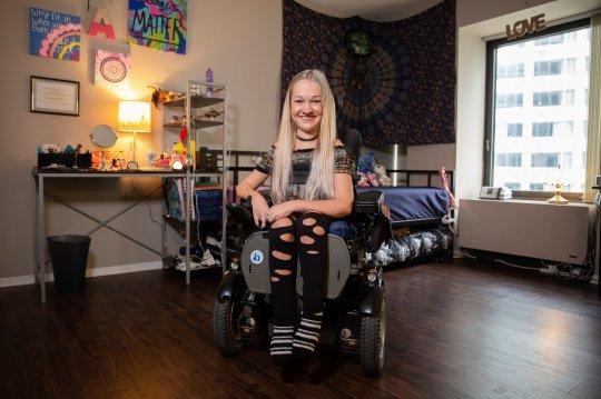 Alex in her bedroom, sitting on her wheelchair