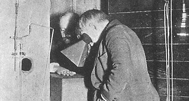 Edison looks through his invention, the fluoroscope, at his the hand of his assistant. Meanwhile, the assistant