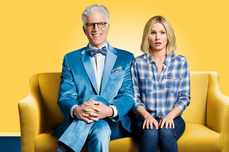 Hombre y una mujer sentados en un sofá sonriendo, escena promocional de la serie The Good Place