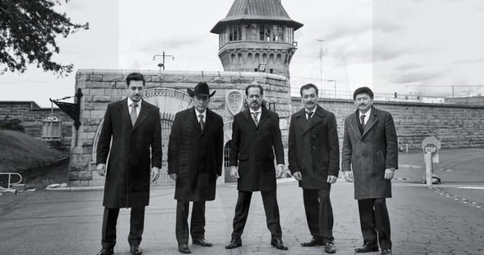 Los Tigres del Norte parados frente a una prisión, escena del documental Los Tigres del Norte en la prisión de Folsom