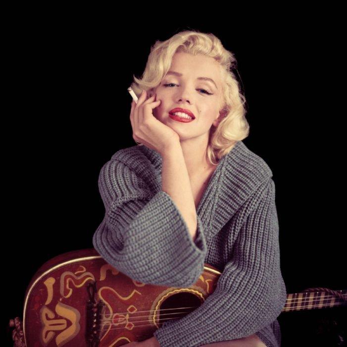 Marilyn Monroe sosteniendo un cigarro y una guitarra