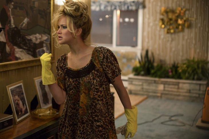 Chica limpiando mientras usa unos guantes amarillos