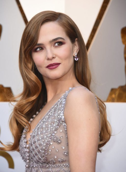Zoey Deutch usando un vestido gris durante la alfombra roja de los premios Oscar
