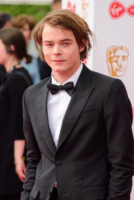 Charlie Heatonusando un traje mientras desfila por la alfombra roja de los premios BAFTA