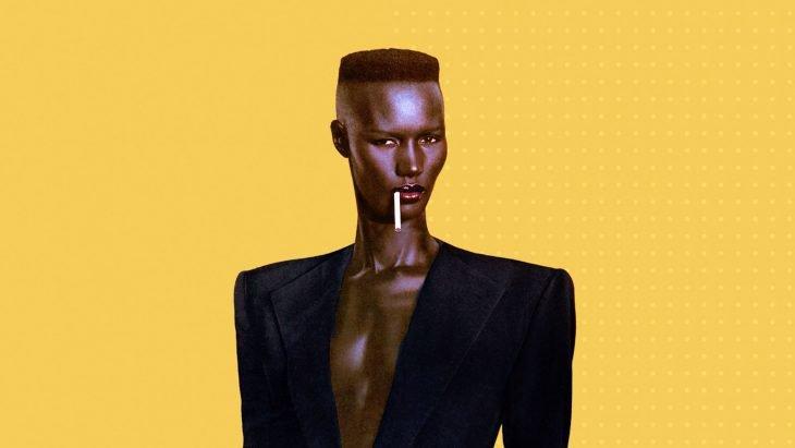 Mujer de color con cabello corto y saco con hombreras sobre fondo amarillo
